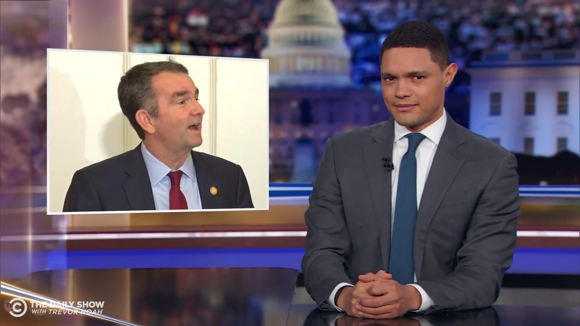 Trevor Noah in front of a photo of Ralph Northam.