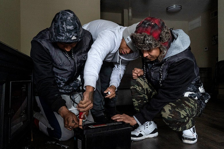 Three men bending over a car battery on the floor in a dark room