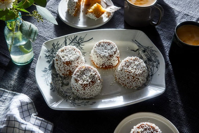 Three pastries on a plate with sugar crystals on top near a cloth and cup.
