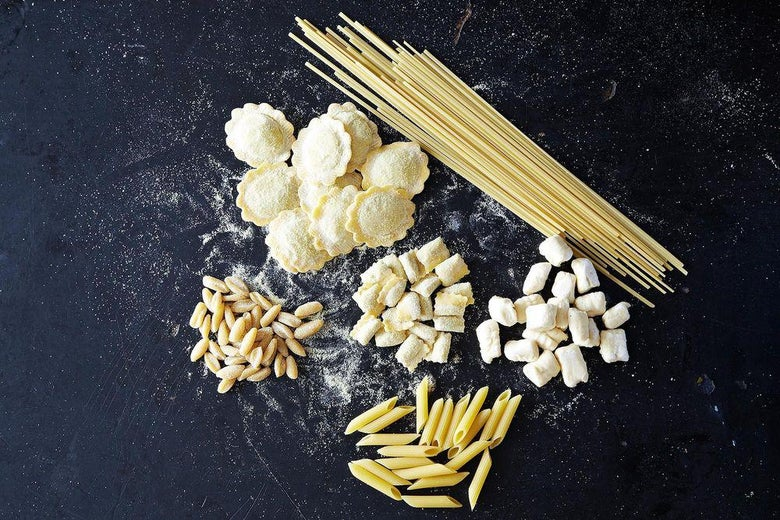 Uncooked penne, spaghetti, and other shapes of pasta on a black surface.