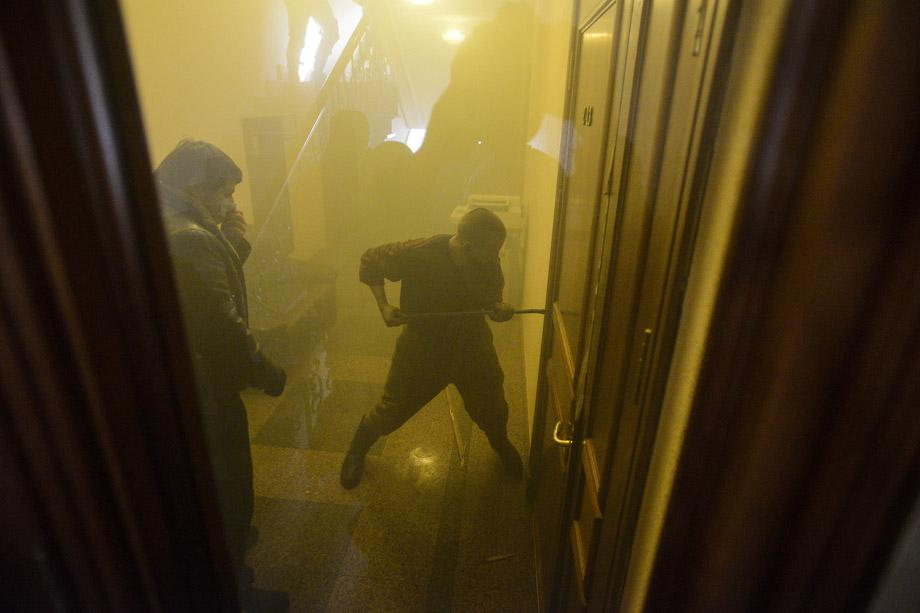 Protesters attempt to break a door inside an office of the pro-presidential Party of the Regions in Kiev on Feb. 18, 2014. UKRAINE/