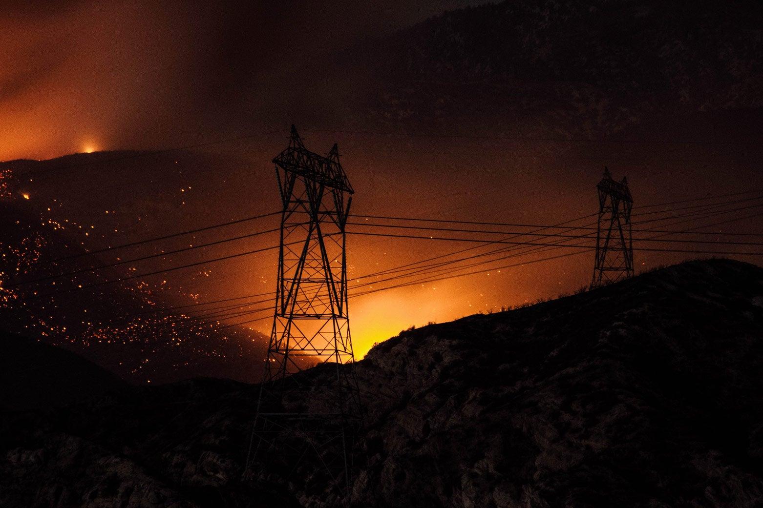 A wildfire burns near power lines.