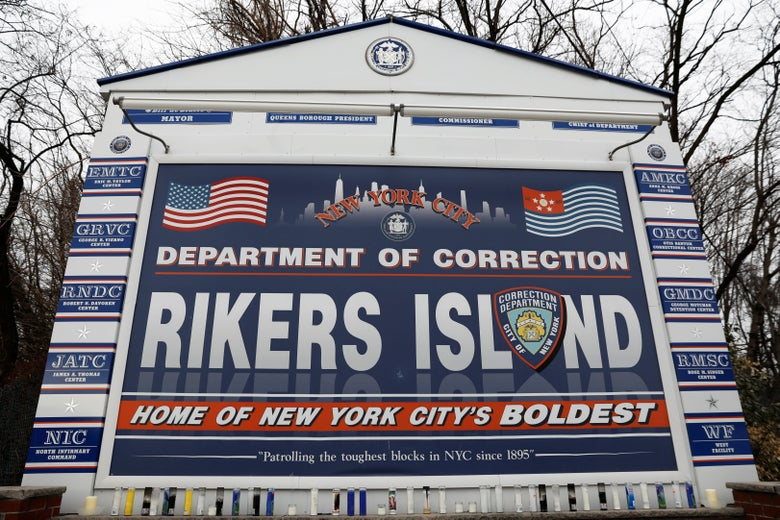 "A big sign says, ""Department of Correction, Rikers Island, Home of New York City's Boldest."""