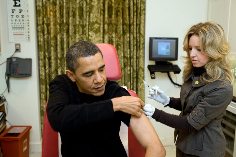 Barack Obama rolls up his sleeve as a woman holds a syringe.