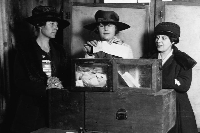 A woman places a ballot in a box as two women on either side of her watch