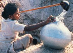 A young girl collecting water from holes dug in the ground.