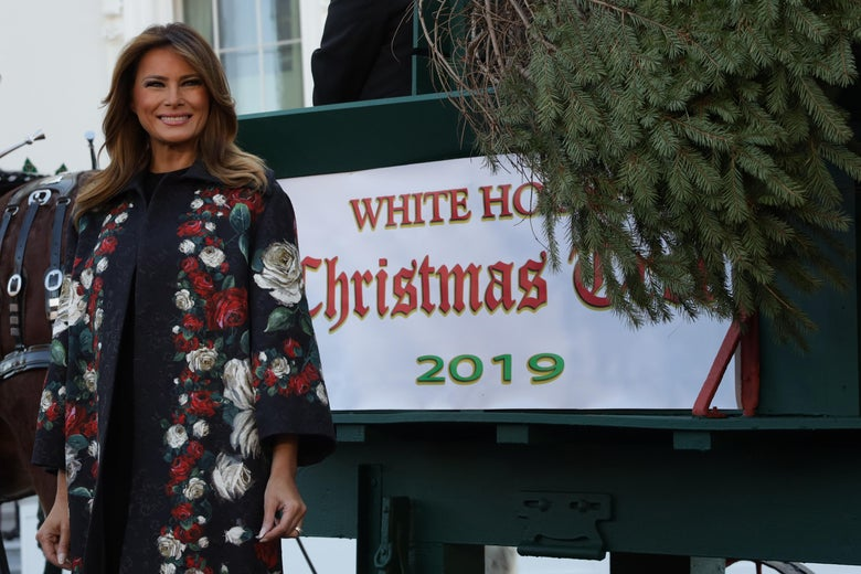 Melania Trump smiles as she receives the 2019 White House Christmas tree outside the White House.