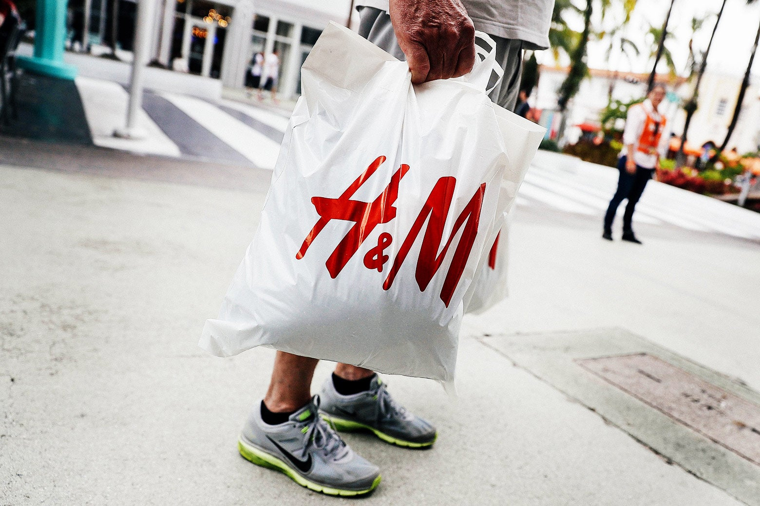 A plastic bag with the H&M logo on it, held by a man in shorts and sneakers outside a store in Miami.