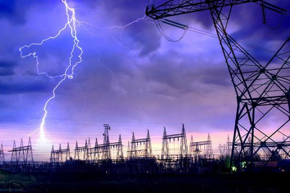 Power distribution station with lightning striking electricity towers.