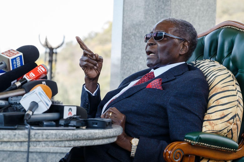 Mugabe slouched back in a chair wearing sunglasses and speaking into a microphone