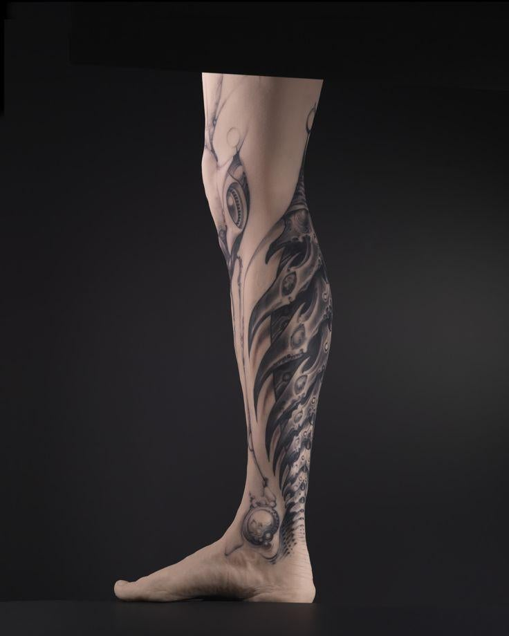 Tattoo designed by Grime on the silicone cast of a man's leg.