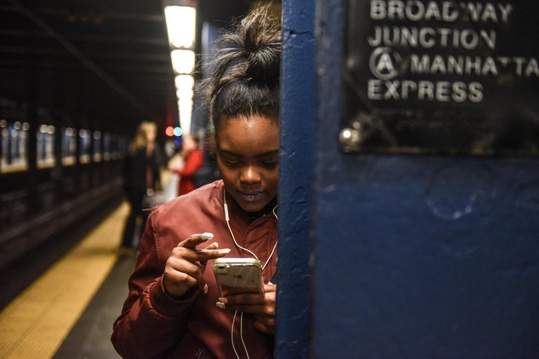 NEW YORK, NY - NOVEMBER 14: A woman looks at her phone while waiting on the platform at the Broadway Junction subway station on November 14, 2019 in New York City. The MTA, which oversees the New York City subway system, the largest in the United States, is reconsidering a plan to hire 500 new transit police officers as they face a $1 billion budget deficit. (Photo by Stephanie Keith/Getty Images)