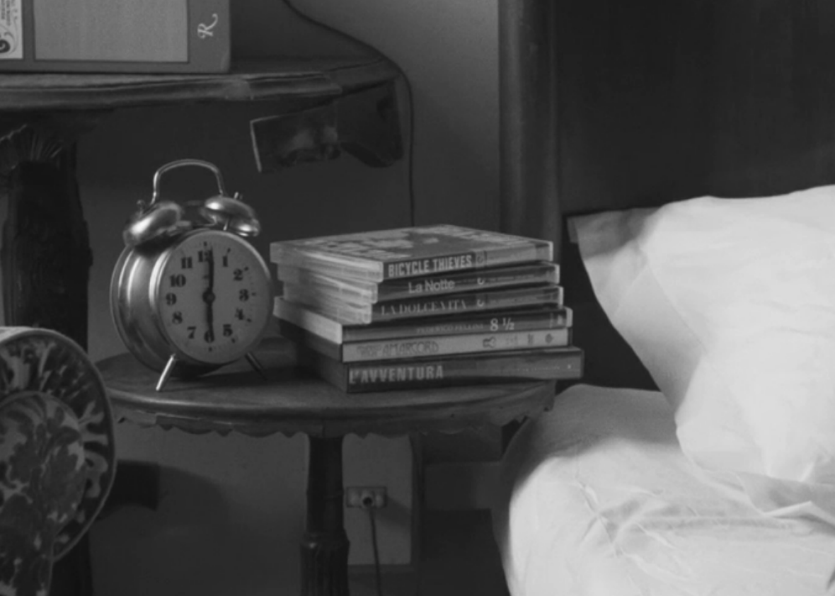 The DVDs on Dev's nightstand: Vittorio De Sica's Bicycle Thieves, Michelangelo Antonioni's La Notte, Federico Fellini's La Dolce Vita, 8½, and Amarcord, and Antonioni's L'Avventura