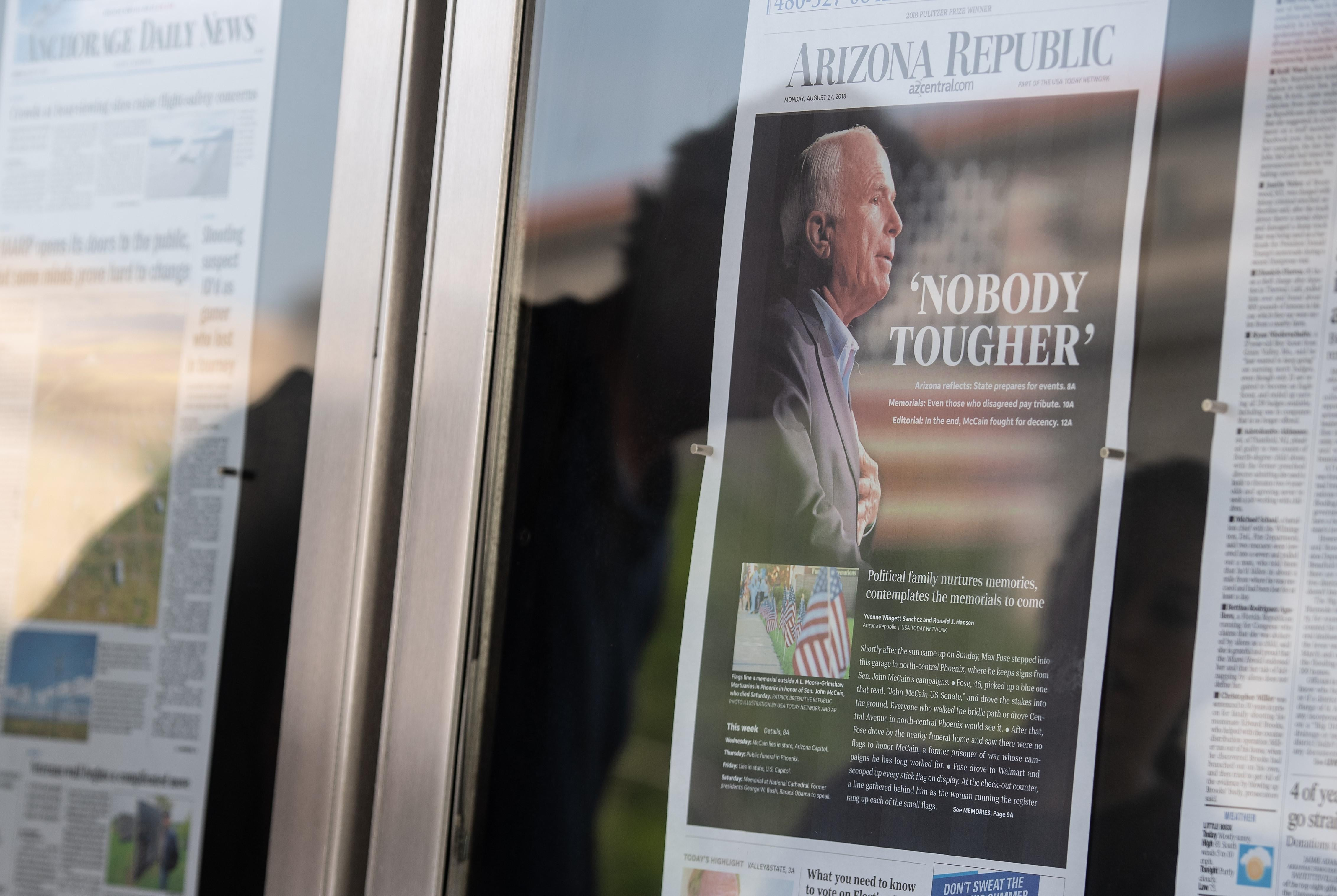 A reflection of people looking at the front page of the Arizona Republic with a picture of John McCain