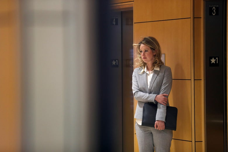 A woman in a gray suit stands in front of elevators, holding a portfolio, with one arm crossed in front of her.