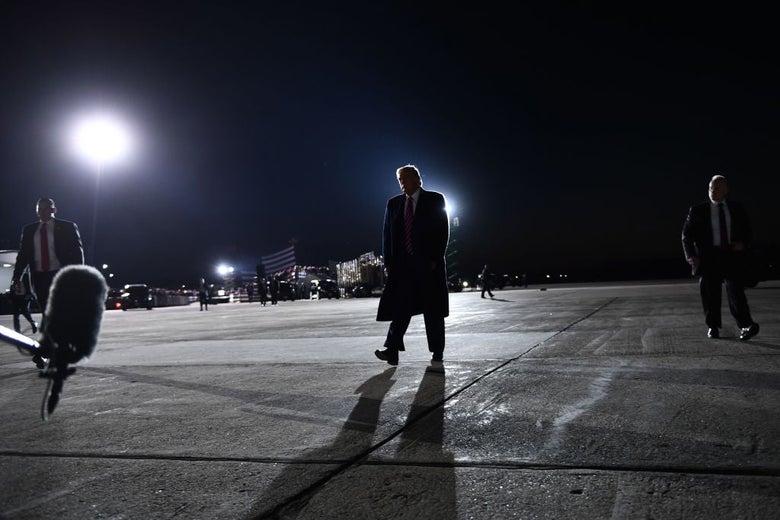 Trump, wearing a long coat, walks across an airport tarmac.