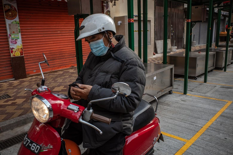 A motorcyclist wearing a face mask looks at his phone while sitting on his bike.