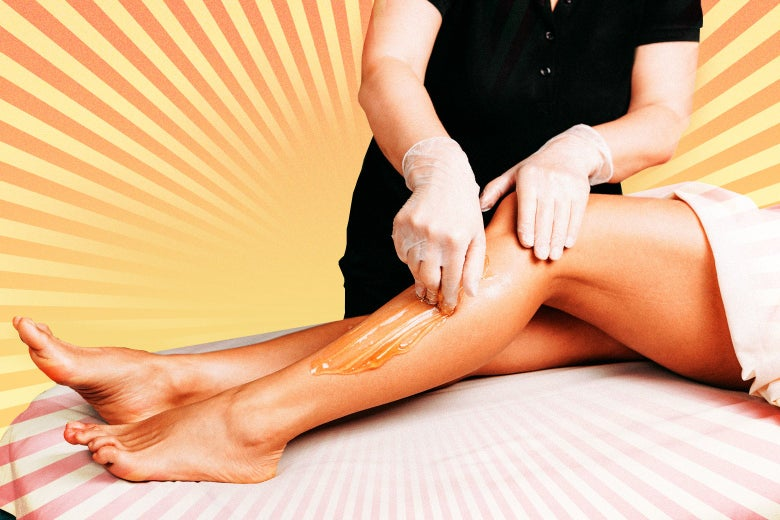 A pair of legs get waxed by a professional.