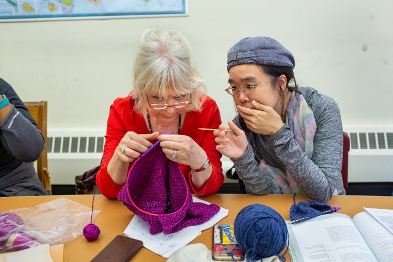 A woman helps another woman with her knitting.