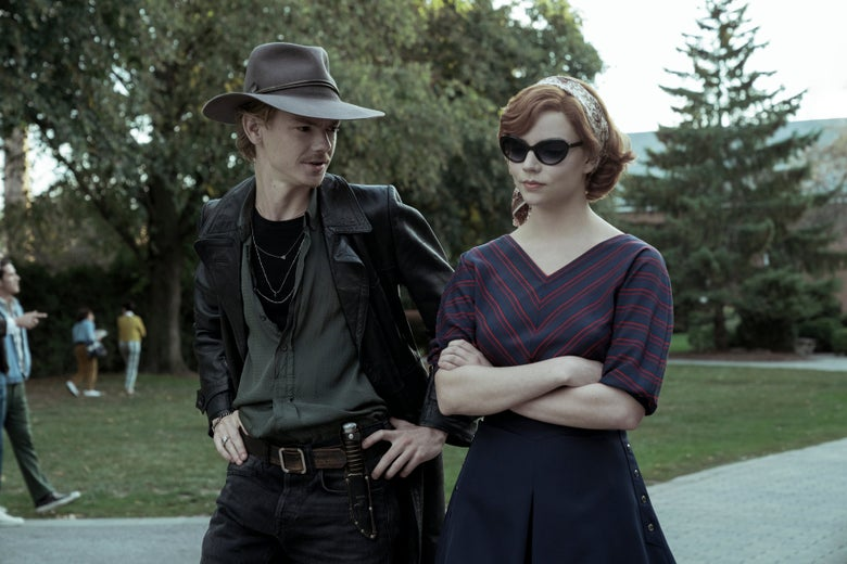A man stands, hands on hips, in a cowboy hat and leather trenchcoat, next to a skeptical woman in sunglasses.