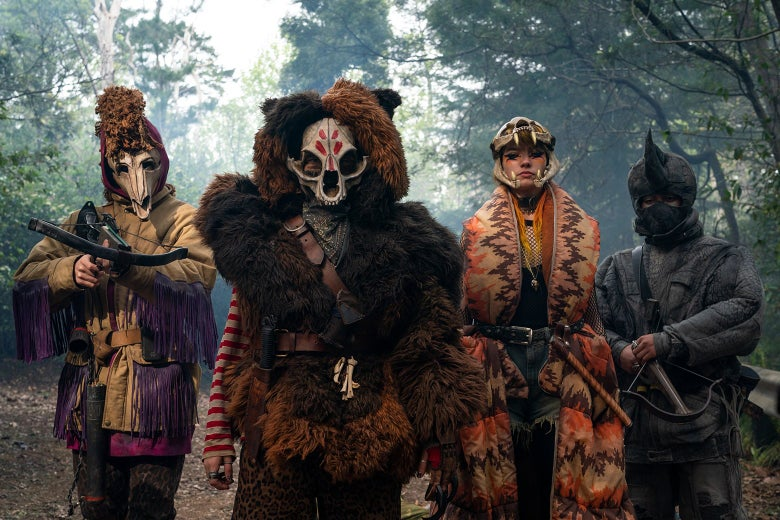 Four children, dressed in fur and wearing animal skulls over their faces, face the camera. The leftmost is aiming a crossbow at the camera.