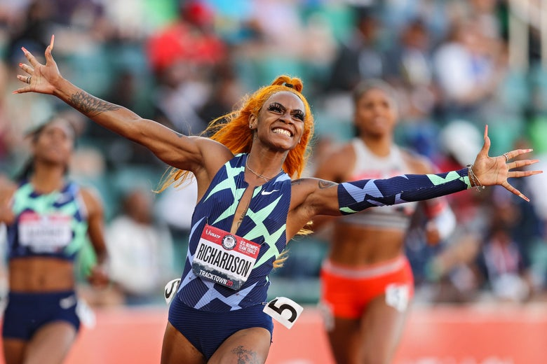 Sha'Carri Richardson raises her arms to celebrate as she crosses the finish line to win the 100-meter women's final.