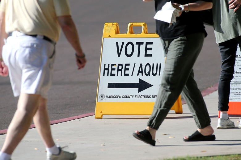 Two individuals walk past a sign that reads VOTE HERE/AQUI.