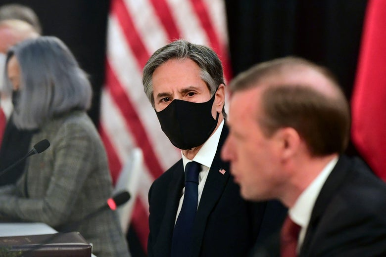 One man in the foreground speaking. Another in the background, in a mask, looking on.