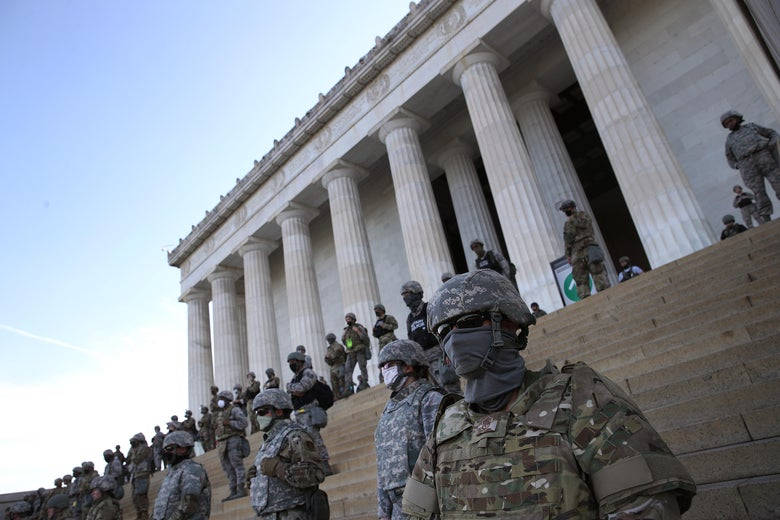 National Guard troops in dark sunglasses on the steps of the Lincoln memorial.