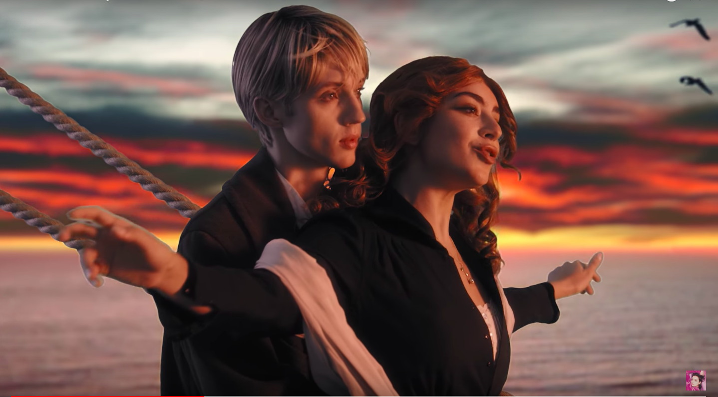Troye Sivan holding Charli XCX's waist as she stands at the front of a ship at sunset.