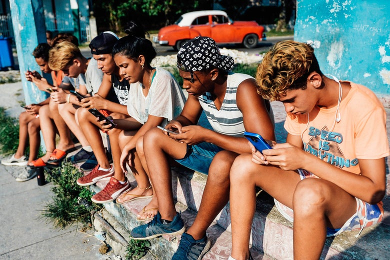 Young Cubans connect to internet from their mobile phones in Havana on June 6.