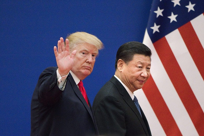 Trump and Xi walking by an American flag. Trump waves to the camera.