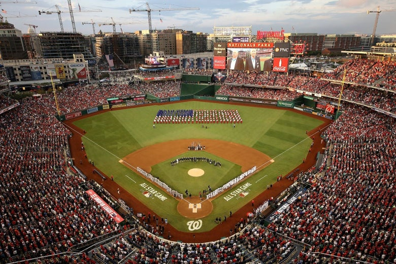 An overhead shot of a capacity crowd at Nationals Park in Washington, D.C. with a large American flag visible in the outfield.