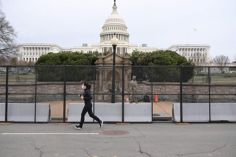 A woman jogs past a tall metal security fence in front of the low stone wall surrounding the Capitol. National Guardsmen in camo patrol the sidewalk between the fence and the stone wall, and the Capitol dome looms in the background.