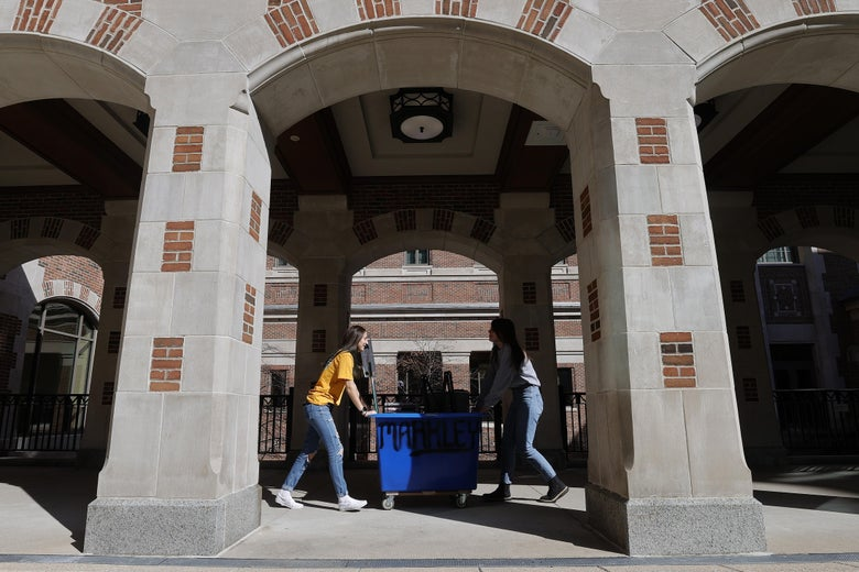 Two women push a cart full of belongings out of a dorm.
