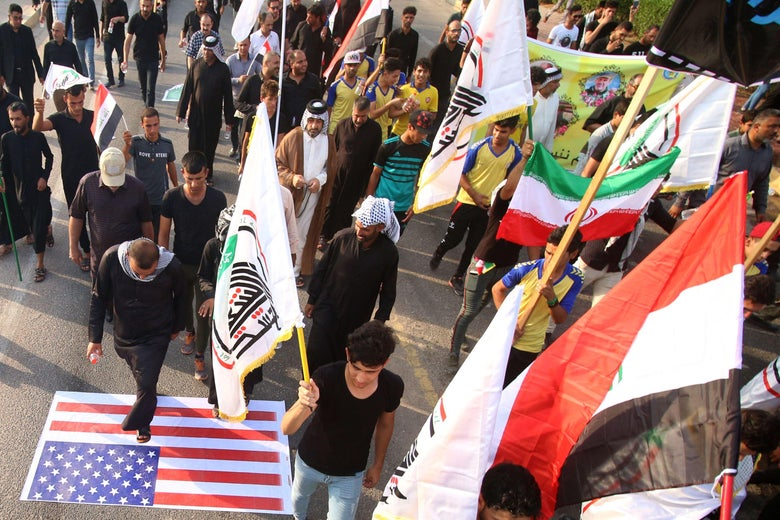 Demonstrators waving Iranian and pro-Iranian party flags step on a U.S. flag as they march