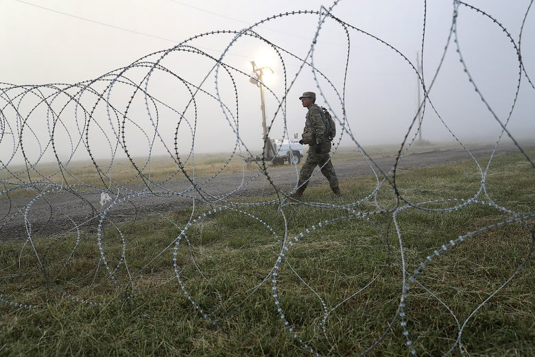 A soldier walking beside a barbed wire fence.