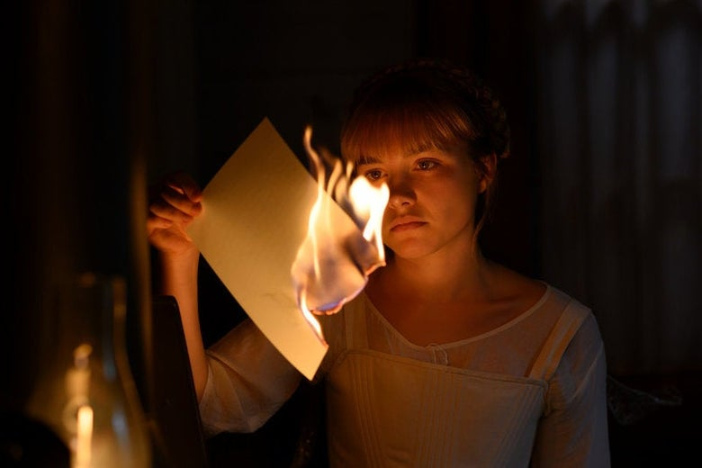 Florence Pugh as Amy March in Little Women, holding a burning piece of paper.