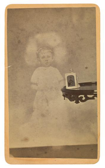 "Child ""spirit"" with photograph and figurine on table."