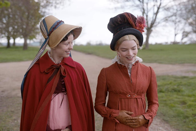 Mia Goth wears a red cloak and a bonnet. Smiling, she looks at Anya Taylor-Joy, who wears a tall hat with a festive ornament on it.