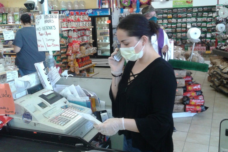 A woman wearing a mask stands behind a cash register and holds a cellphone up to her ear.