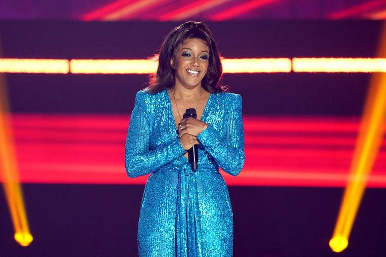A woman with brown hair and an updo wears a sparkly blue dress. She stands on a stage with red and yellow lights.