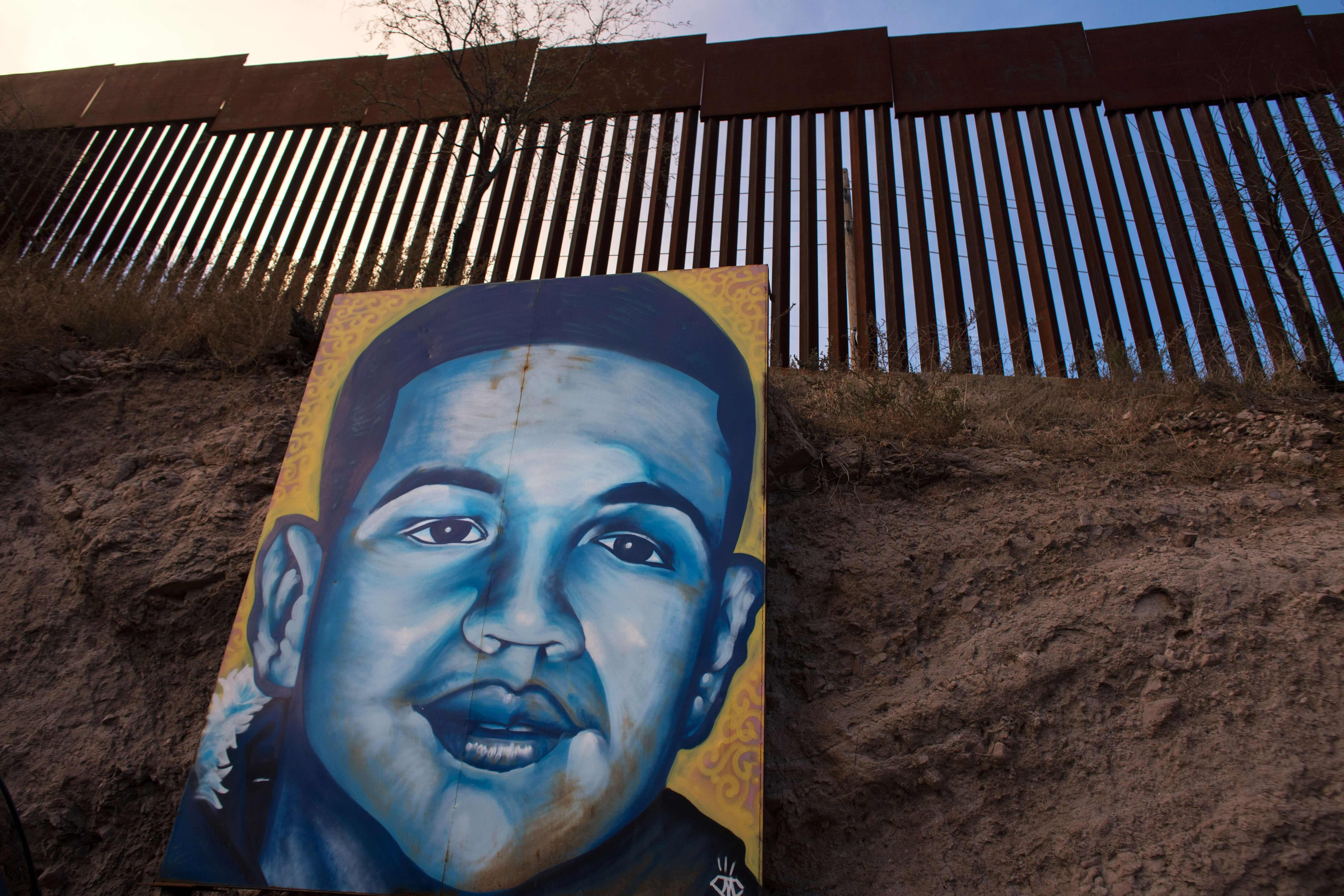 A large portrait of a teenage boy, painted in blues on a yellow background, leans against earth under a border fence.