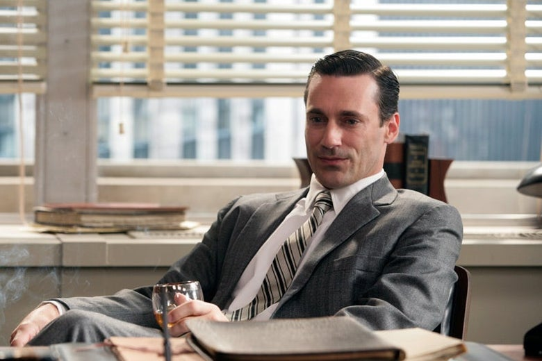 Jon Hamm in a grey suit sits behind a desk, a glass of brandy in hand.