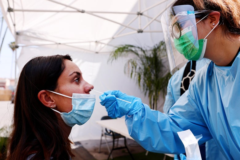 A nurse wearing personal protective equipment inserts a COVID testing swab into a woman's nostril.