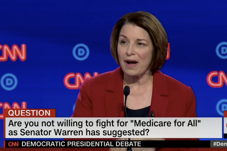 "In this screengrab from CNN, Amy Klobuchar debates. The banner reads: ""Are you not willing to fight for 'Medicare for All' as Senator Warren has suggested?"""