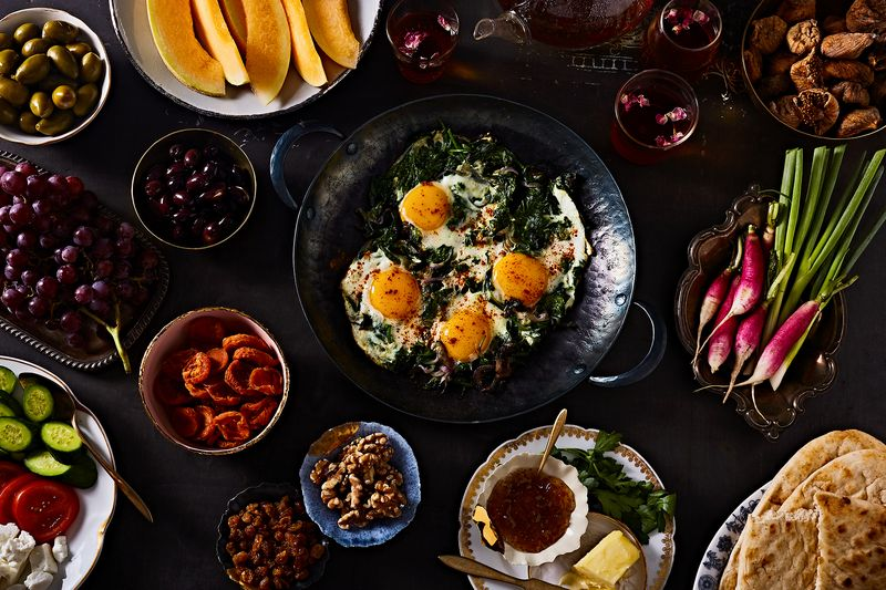Saucepan with singed fried eggs and spinach on table surrounded by lots of bowls of food including orange cantaloupe slices, green olives, bright pink radishes and walnuts