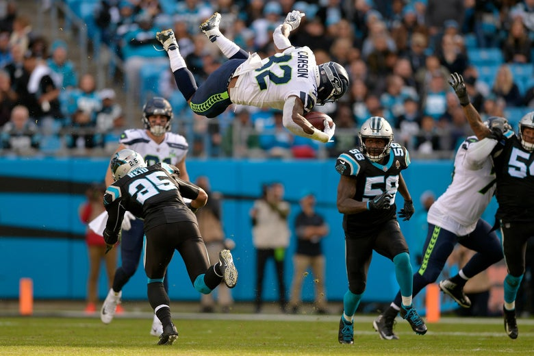 CHARLOTTE, NC - NOVEMBER 25:  Chris Carson #32 of the Seattle Seahawks runs the ball against Eric Reid #25 and Thomas Davis #58 of the Carolina Panthers in the third quarter during their game at Bank of America Stadium on November 25, 2018 in Charlotte, North Carolina.  (Photo by Grant Halverson/Getty Images)