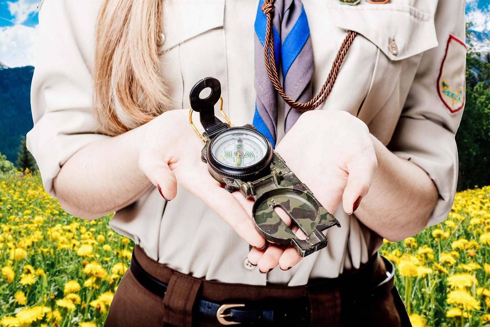 A Girl Scout holds a compass.