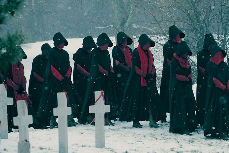 Handmaids walk through the snow in The Handmaid's Tale.